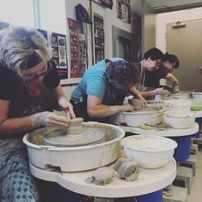 Picture of a group of students throwing on the potters wheel.