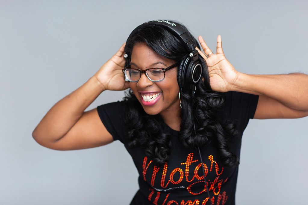 Robin Kinnie with headphones on and black and red Motor City Woman shirt.