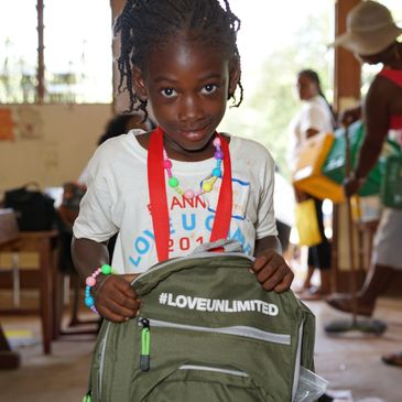 A child holding a new backpack