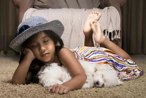 Little girl and puppy sleeping on clean carpet