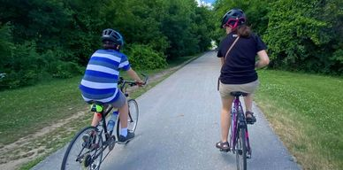 The backs of two children with masks as they ride down a bike path.