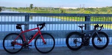 Two bikes leaning against the rail of a bridge over a river.