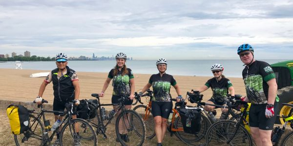 Five cyclists standing with bikes along Lake Michigan. Chicago skyline in the distance.