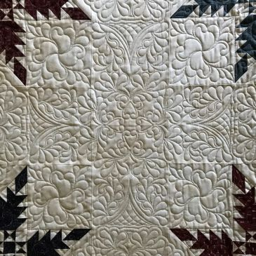 Custom quilting on a Liberty quilt top.