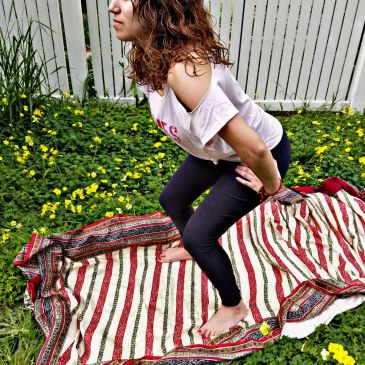 The position for one of the Tantric movements shown by a student outside on the grass surrounded by little yellow flowers.