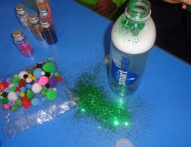 water bottle with glitter and coloured beads. Children are making a larva bottle.