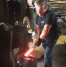 Tony Majors using the power hammer in the shop.