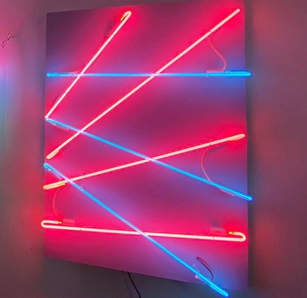 Pink and blue neon crisscrossed like lasers mounted on a pale blue backdrop