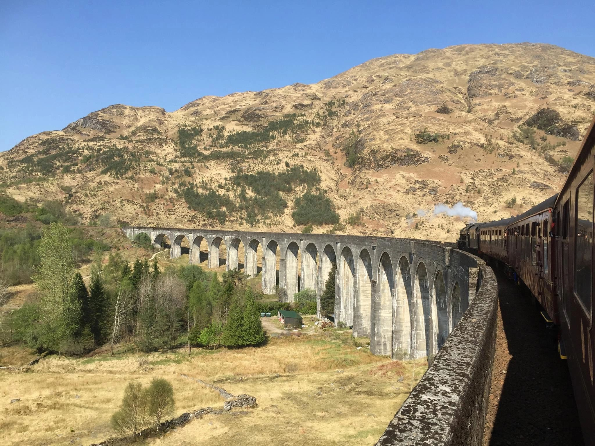 The jacobite Steam Train travelling over Glenfinnan Viaduct or harry Potter bridge and blue skies