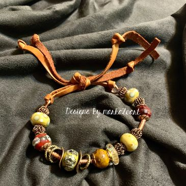 Lampwork beads and spacer beads strung on heavy gauge wire make up this one of a kind bracelet cuff