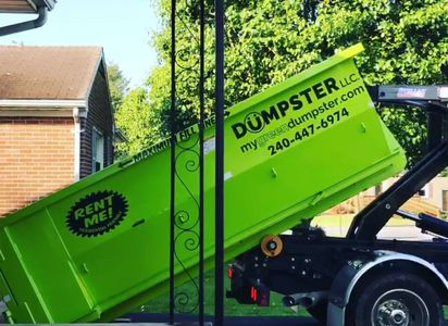 Rental of a 9yard green dumpster safely placed on an asphalt driveway