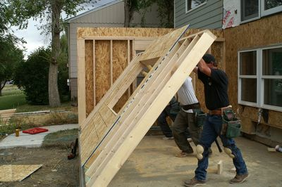 construction workers lift exterior frame wall on home addition