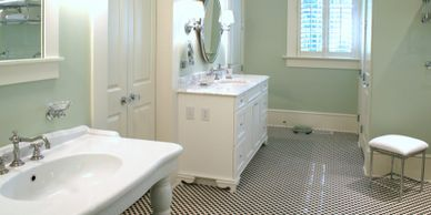 pale green bathroom walls multiple white sinks and vanities black and white classic tile floor
