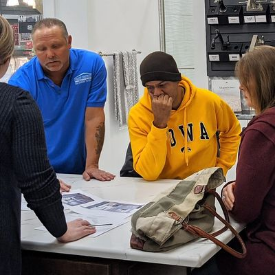 General contractor in blue shirt with homeowners reviewing kitchen design plan in dubuque  iowa