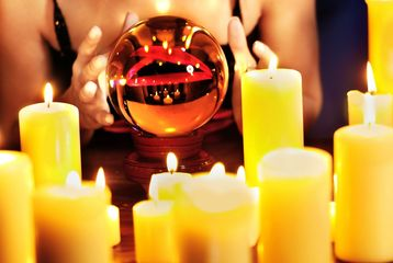 A psychic woman's hands around a crystal ball with many lit candles in the foreground.