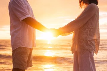 Couple holding hands in front of the sun setting over the ocean