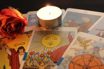 Tarot cards showing the sun and people arranged on a table with a burning candle and red rose.