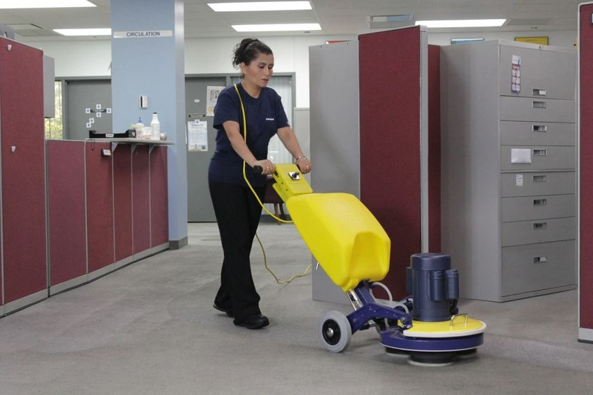 Woman using a low moisture carpet cleaning machine to clean commercial carpeting in san angelo, tx.