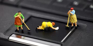 miniature housekeepers sweeping and mopping the keyboard on a laptop