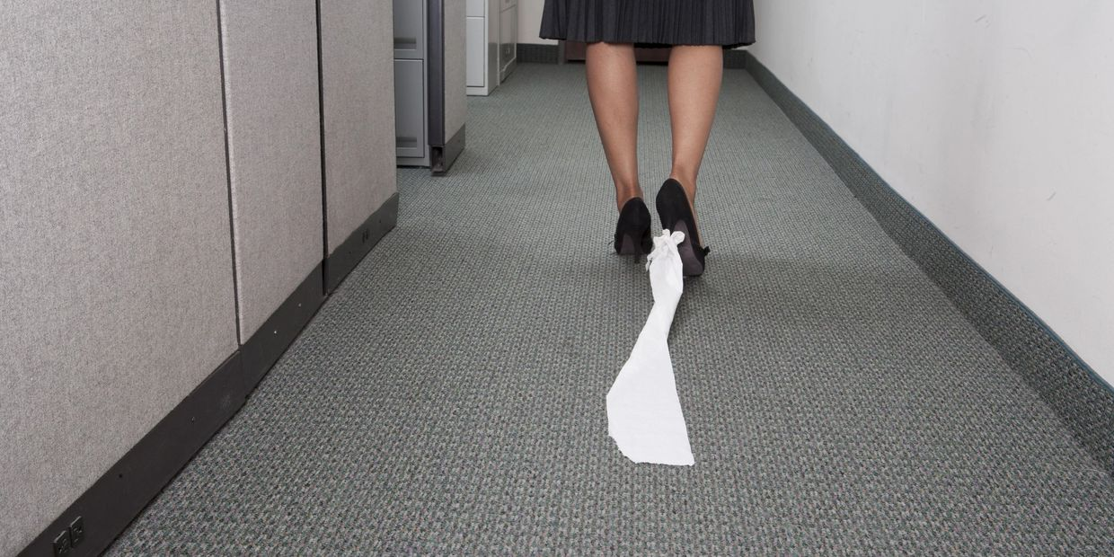 Woman walking down a carpet hallway with a length of toilet tissue tuck to the heel of her shoe.