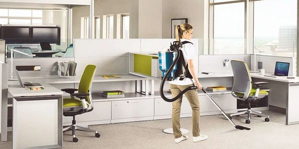 office cleaning lady using a vacuum to clean an office space