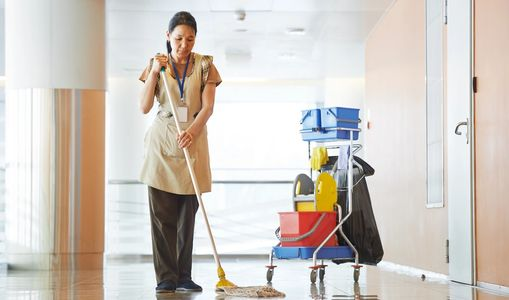 Woman mopping the floor of a commercial cleaning account.