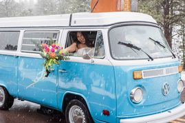 Bride holding bouquet out window of old VW bus