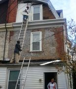 Alex is up on the ladder repairing the back of the three-story home in Philadelphia.