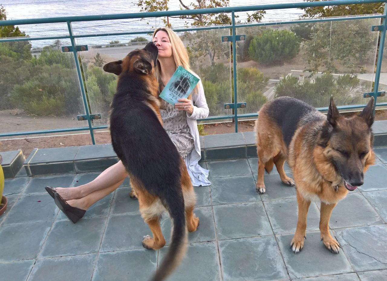 Author Claire Fullerton at her oceanfront home  with her pups in Malibu, CA.