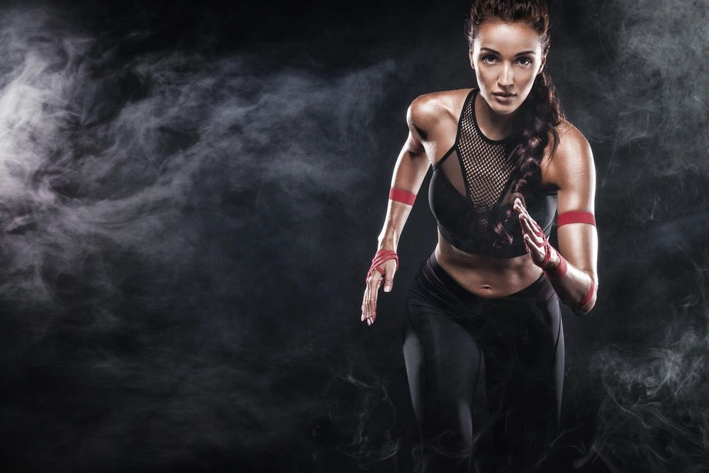 A strong athletic, woman sprinter, running on black background wearing in the sportswear