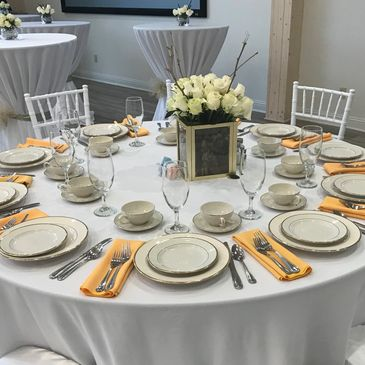 White linen on round table with china dinner plate, salad plate, cup, saucer, wine glass and silverware. White flower centerpiece gold napkins