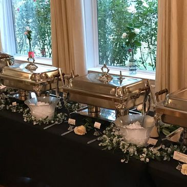 Wedding Buffet table with black linens, white flowers, and silver decorations