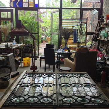 The main studio at Feldman Stained Glass located in Jersey City, NJ with  restored set of stained glass windows which include rondels glazed in lead cames.