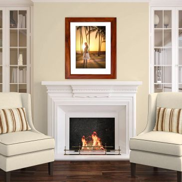 Wood-framed portrait of a young woman in Hawaii above a white fireplace in a beautiful sitting room.