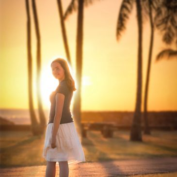 Magnified image of a portrait of a young woman turned away from the bright sunset in Hawaii