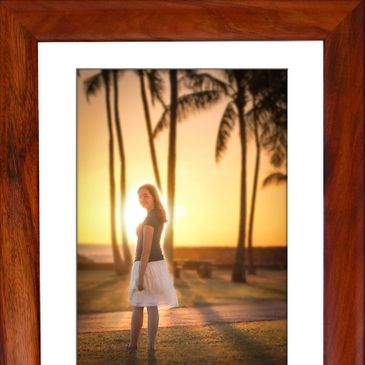 Portrait of a young woman turning from the bright sunset in Hawaii set in a wood frame