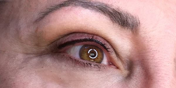 Woman with permanent lash enhancement eyeliner on her eye