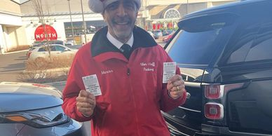 happy valet attendant in an alber-haff uniform holding two claim checks at the king of Prussia mall