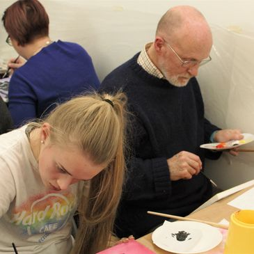 An art class, painting class. Granddad and daughter learn to paint in family art class in Edinburgh.