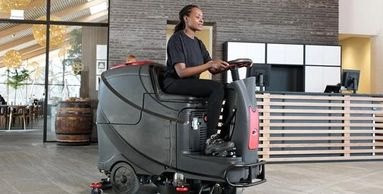 Woman driving a floor scrubber in a commercial lobby