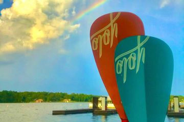 the end of paddle board paddles held up agains the background of a sky with a rainbow in the sky