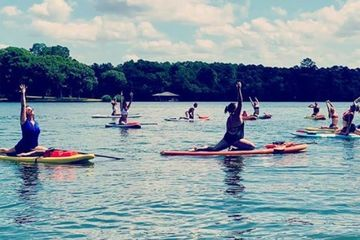 a group of people doing yoga on a lake while on paddle boards