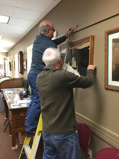 Volunteers hang art in Meeting Room