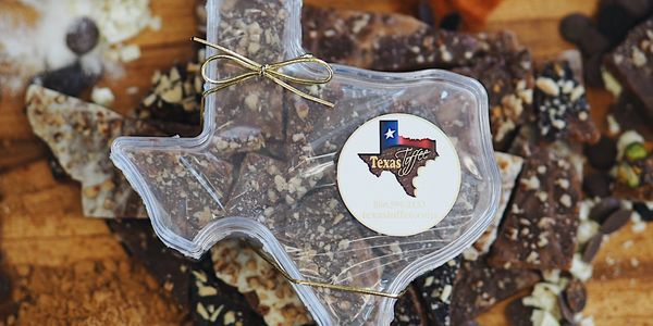 Texas Toffee Lucite filled with pecan toffee with custom label and gold tie along with sugar, butter, milk chocolate and dark chocolate coins, cayenne pepper, ghost pepper, habanero pepper, milk chocolate macadamia nuts, almonds, pistachios.
