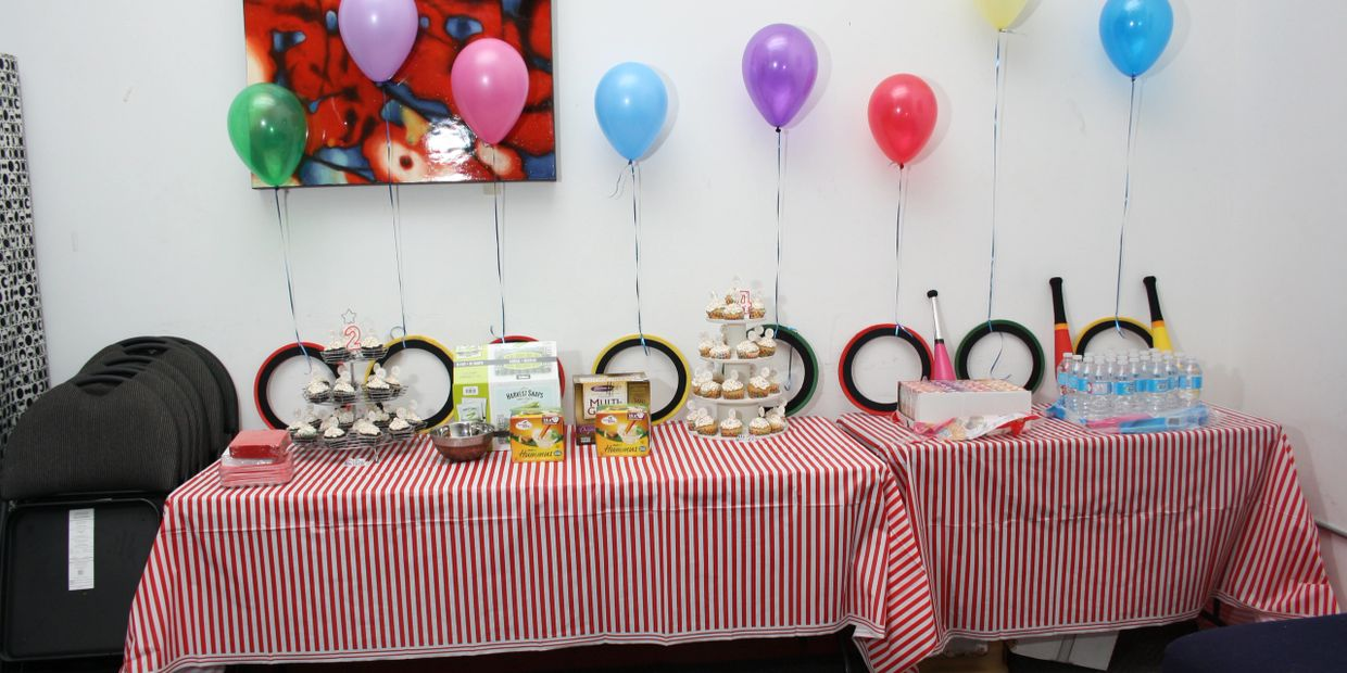 Table set up with cupcakes, food, balloons, juggling equipment at a kids circus birthday party