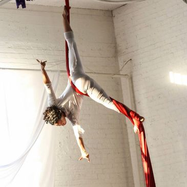 Silks class performer hangs upside down on the fabric with no hands in a Straddle split stretch