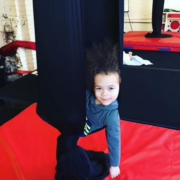 A Kindergym kid smiles while wrapped up in an aerial hammock cocoon pose on the silks
