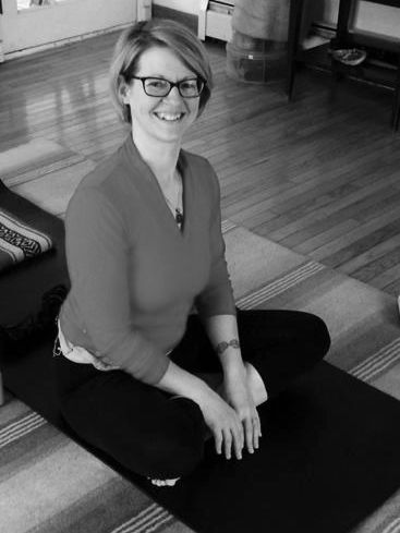 a black and white photo of Heather Horton, LMT sitting on a yoga mat and smiling