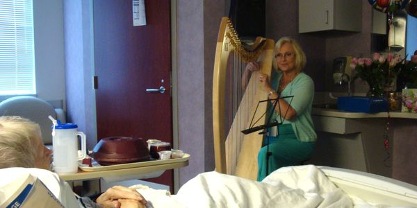 Certified Music Practitioner playing Live Therapeutic Music on a Harp for a patient in a hospital bed