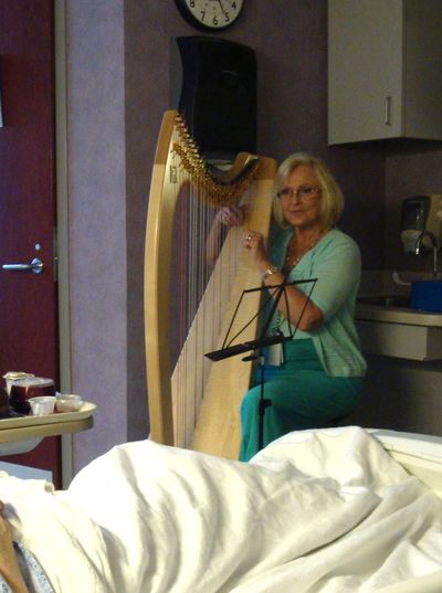 Certified Music Practitioner playing Live Therapeutic Music on a harp in a hospital room